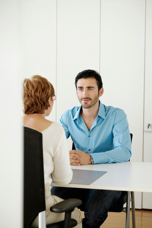 Man sitting opposite woman in office Stock Photo