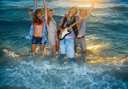 Young group sing with guitar in tide sea Reklamní fotografie