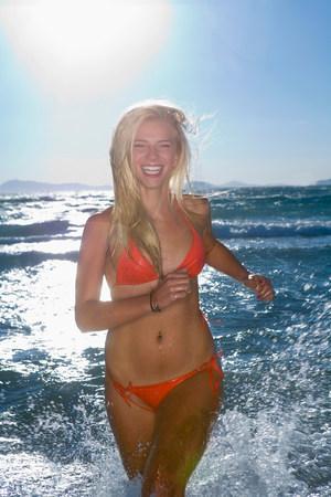 Happy healthy women runs at sea