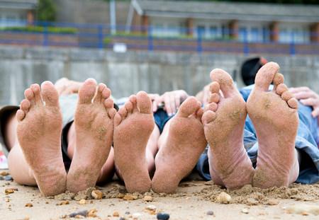 Families sandy feet on beach