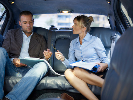 Businessman signing paper in limousine