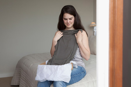 Woman holding up shirt from package