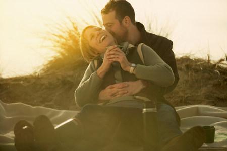Couple on beach cuddling. With coffee