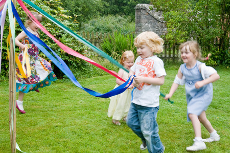 Children dancing round a maypole Stock Photo