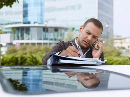 Businessman with paperwork on top of car