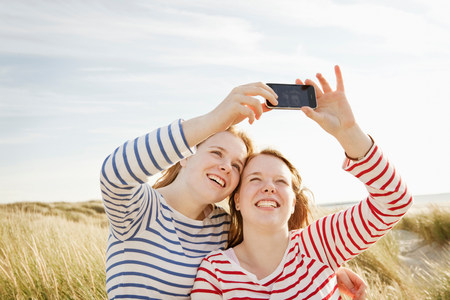 Teenagers taking self-portrait on mobile