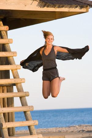 Beautiful girl jumping beach 免版税图像