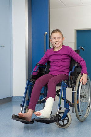 Girl in wheelchair, foot in plaster 스톡 콘텐츠