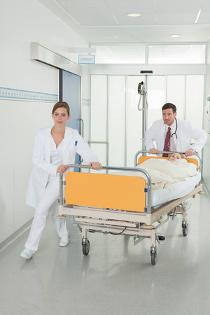 Nurse and doctor pushing bed in hall