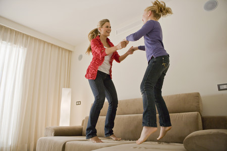 Young woman and girl jumping on sofa 免版税图像