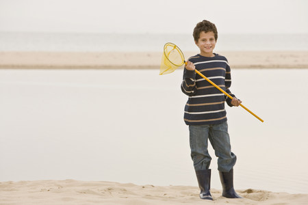Young boy at beach holding fishing net Stock Photo