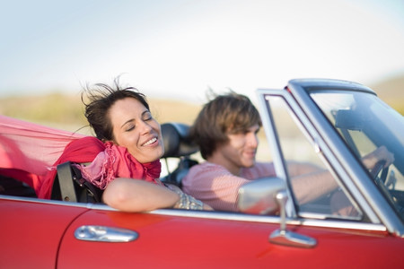 Man and woman driving in a convertible