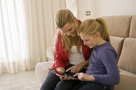 Woman and girl using tablet computer Stock Photo