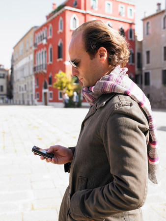 Man looking at his phone in the street