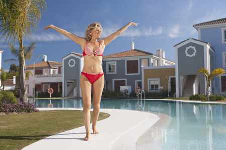 Woman with arms stretched out by pool