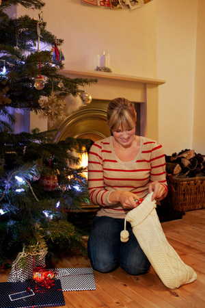 A woman reaching into a xmas stocking