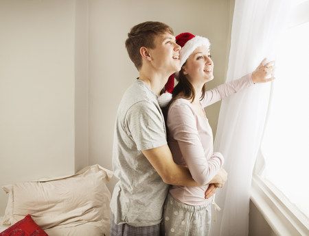 Couple embracing, looking out of window
