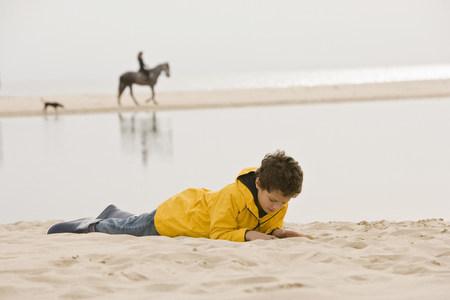 Young boy lying on sand at beach Stok Fotoğraf