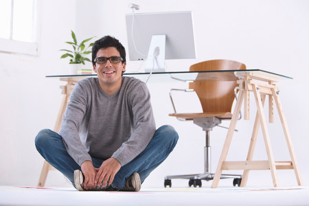 Man sitting on the floor smiling in an office