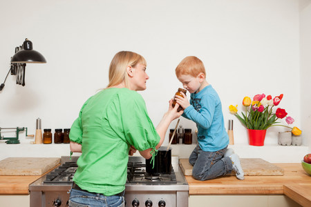 Woman cooking with son in kitchen