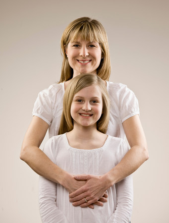 Smiling mother hugging daughter Stock Photo