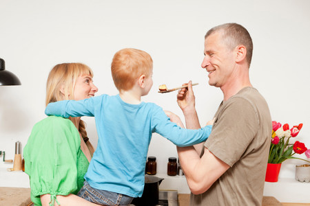 Family cooking together in kitchen Stock Photo