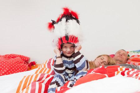 Boy wearing war bonnet in parents? bed