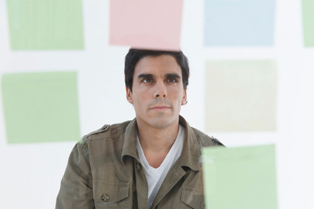 Man looking at different coloured post-it notes