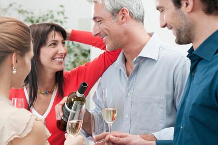 Happy smiling friends drinking wine