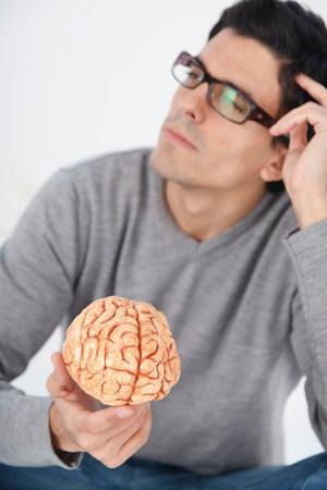 Man holding model brain, thinking Zdjęcie Seryjne