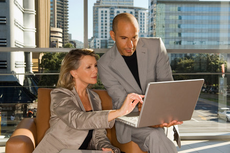 Businessman and woman looking at laptop