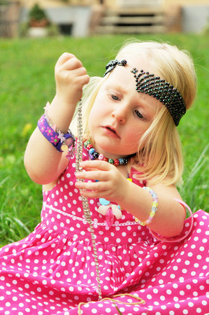 Girl playing with jewelry in backyard