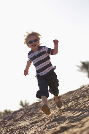 Boy in sunglasses running on beach