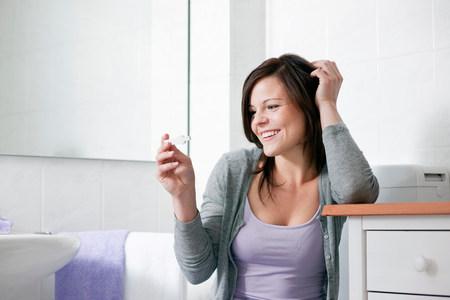 Smiling woman taking pregnancy test Banque d'images - 113989576
