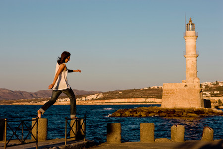 woman balancing on stones in front of a lighthouse