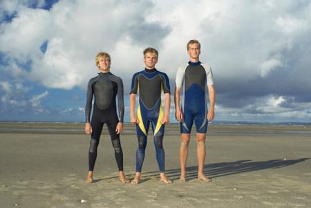 Surfers standing in row on beach 版權商用圖片