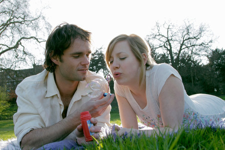 Couple blowing bubbles in grass at park