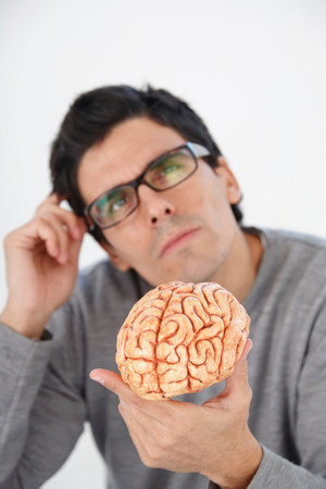 Man holding model brain, thinking Imagens