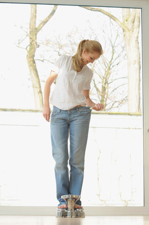 Woman wearing large jeans on scale