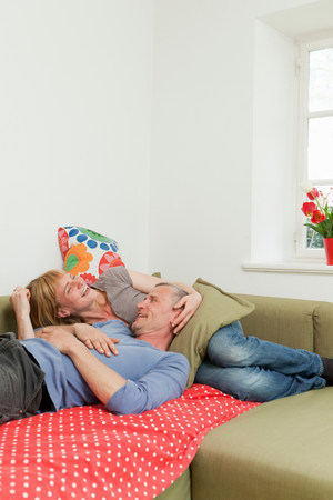 Couple relaxing together on sofa Stock Photo