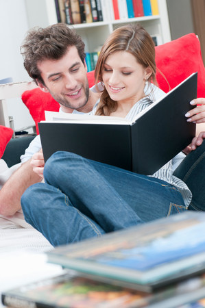 Couple reading together a book on sofa Stock Photo