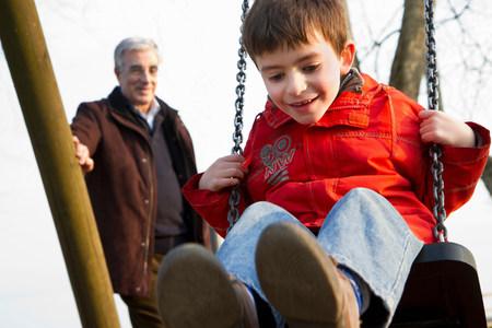 Man pushing grandson on swing at park 免版税图像