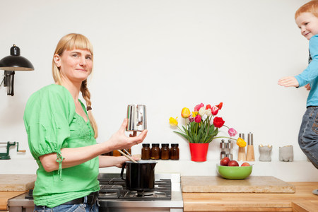 Woman cooking as son plays in kitchen
