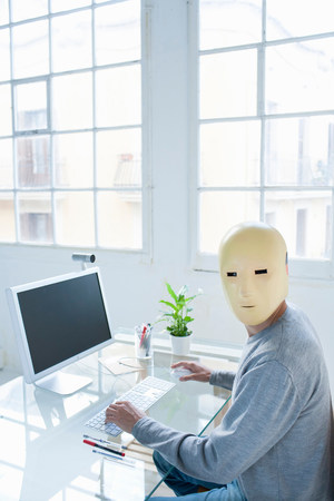 Man in crash test dummy mask in an office Banco de Imagens