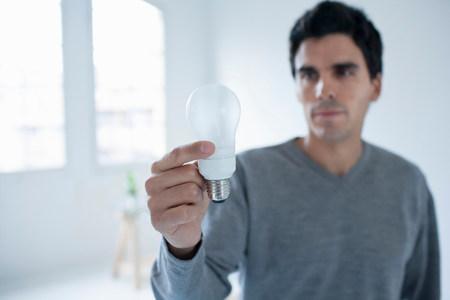 Man holding a light bulb Reklamní fotografie