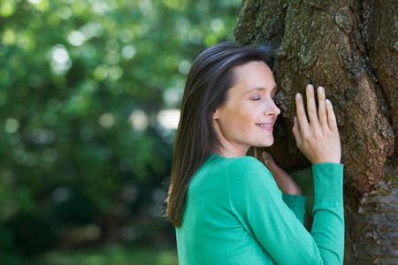 Smiling woman hugging tree