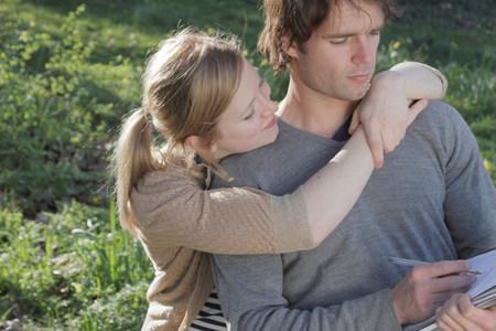 Woman hugging writing boyfriend