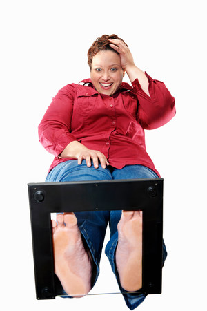 Smiling large woman standing on scales
