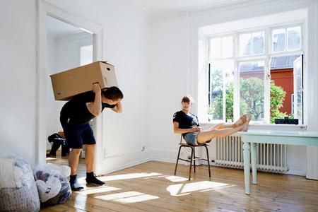 Woman watching boyfriend carry heavy box