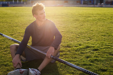 Man sitting with pole on grass Stock Photo